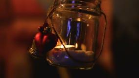 Μικρό διακοσμημένο βάζο με το κερί μέσα να ταλαντευθεί στον αέρα, ρομαντικό φως τη νύχτα απόθεμα βίντεο
