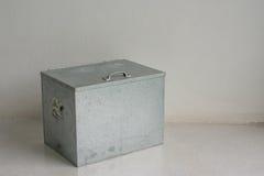 Μικρό εμπορευματοκιβώτιο μετάλλων στο τσιμεντένιο πάτωμα στο άσπρο δωμάτιο Στοκ Φωτογραφία