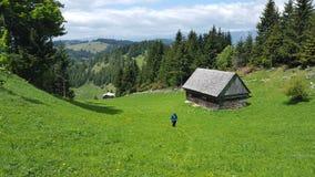 Μικρό εξοχικό σπίτι στο συμπαθητικό λιβάδι βουνών Στοκ εικόνες με δικαίωμα ελεύθερης χρήσης