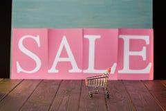 Μικρό κάρρο αγορών με το σημάδι πώλησης στον ξύλινο πίνακα Στοκ Φωτογραφία