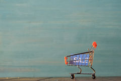 Μικρό κάρρο αγορών με το σημάδι πώλησης στον ξύλινο πίνακα Στοκ Εικόνες