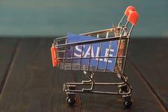 Μικρό κάρρο αγορών με το σημάδι πώλησης στον ξύλινο πίνακα Στοκ φωτογραφίες με δικαίωμα ελεύθερης χρήσης