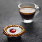 Μικρό κέικ κερασιών με ένα γυαλί του φρέσκου espresso Στοκ φωτογραφία με δικαίωμα ελεύθερης χρήσης