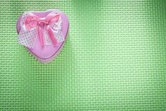 Μικρό καρδιά-διαμορφωμένο ροζ παρόν κιβώτιο μετάλλων στην πράσινη επιφάνεια holid Στοκ Εικόνες