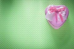 Μικρό καρδιά-διαμορφωμένο ροζ παρόν κιβώτιο μετάλλων στο πράσινο υπόβαθρο ho Στοκ εικόνες με δικαίωμα ελεύθερης χρήσης
