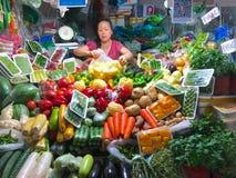 Μικρό κατάστημα στάσεων λαχανικών με τον ιδιοκτήτη γυναικών του καταστήματος στοκ εικόνα