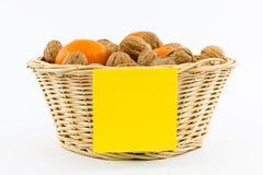 Μικρό καλάθι με τα ξύλα καρυδιάς, Tangerines και την κίτρινη σημείωση Στοκ εικόνες με δικαίωμα ελεύθερης χρήσης