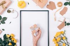Μικρό κιβώτιο δώρων με τα τόξα σε ένα θηλυκό χέρι Στοκ Φωτογραφίες
