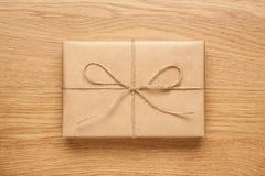 Μικρό κιβώτιο δώρων που τυλίγεται στο έγγραφο του Κραφτ για τον ξύλινο πίνακα στοκ εικόνες