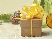 Μικρό κιβώτιο δώρων της Kraft με την κίτρινη κινηματογράφηση σε πρώτο πλάνο τόξων στο υπόβαθρο ο Στοκ Εικόνες