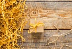 Μικρό κιβώτιο δώρων τεχνών στον ξύλινο πίνακα με raffia Στοκ Φωτογραφία