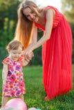Μικρό κορίτσι δίπλα στη μητέρα της στο χορτοτάπητα στο πάρκο Στοκ Φωτογραφίες