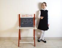 Μικρό κορίτσι δίπλα στον πίνακα κιμωλίας Στοκ Εικόνες