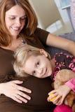 Μικρό κορίτσι και έγκυο χαμόγελο μητέρων Στοκ Εικόνες