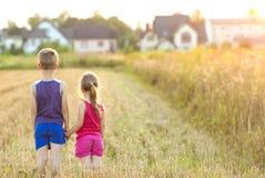 Μικρό κορίτσι και αγόρι standind στον τομέα με το χρυσό φως του ήλιου Στοκ εικόνα με δικαίωμα ελεύθερης χρήσης