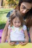 Μικρό κορίτσι και γυναίκα που προσέχουν την κινητή συνεδρίαση στο πάρκο Στοκ φωτογραφία με δικαίωμα ελεύθερης χρήσης