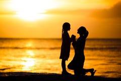 Μικρό κορίτσι και ευτυχής σκιαγραφία μητέρων στο ηλιοβασίλεμα στην παραλία Στοκ φωτογραφία με δικαίωμα ελεύθερης χρήσης