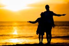Μικρό κορίτσι και ευτυχής σκιαγραφία μητέρων στο ηλιοβασίλεμα στην παραλία Στοκ Εικόνες