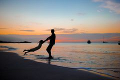 Μικρό κορίτσι και ευτυχής σκιαγραφία πατέρων στο ηλιοβασίλεμα στην παραλία Στοκ Φωτογραφία