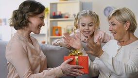 Μικρό κορίτσι και η μητέρα της που παρουσιάζουν το δώρο στη γιαγιά, αξέχαστη στιγμή απόθεμα βίντεο