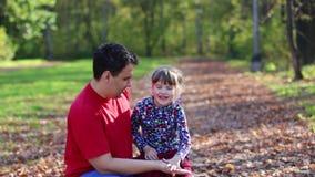 Μικρό κορίτσι και τα χέρια και το παιχνίδι κυμάτων πατέρων της στο ηλιόλουστο πάρκο φθινοπώρου απόθεμα βίντεο