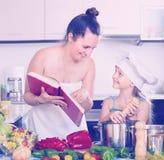 Μικρό κορίτσι και mom με το βιβλίο μαγειρικής Στοκ Φωτογραφίες