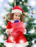 Μικρό κορίτσι κοντά στο χριστουγεννιάτικο δέντρο με ένα δώρο Στοκ εικόνες με δικαίωμα ελεύθερης χρήσης