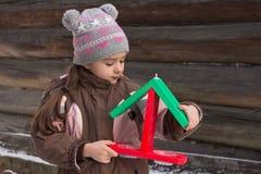 Μικρό κορίτσι με έναν ξύλινο τροφοδότη πουλιών Στοκ Εικόνα