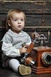 Μικρό κορίτσι με ένα αναδρομικό τηλέφωνο Στοκ Φωτογραφία