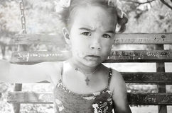 Μικρό κορίτσι με ένα βρώμικο πρόσωπο και τόξα σε μια ταλάντευση Στοκ εικόνα με δικαίωμα ελεύθερης χρήσης