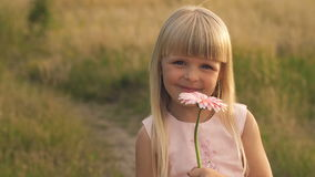 Μικρό κορίτσι με ένα λουλούδι στη φύση