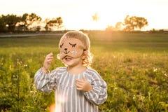 Μικρό κορίτσι με ένα παιχνίδι μασκών στοκ εικόνα