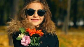 Μικρό κορίτσι με λουλούδια στη φύση