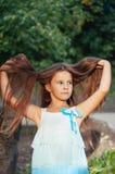 Μικρό κορίτσι με μακρυμάλλη στο πορτρέτο φορεμάτων, τρίχα ανελκυστήρων επάνω, φυσικός φωτισμός υπαίθρια στοκ εικόνες