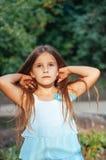 Μικρό κορίτσι με μακρυμάλλη στο πορτρέτο φορεμάτων, τρίχα ανελκυστήρων επάνω, φυσικός φωτισμός υπαίθρια στοκ εικόνες με δικαίωμα ελεύθερης χρήσης