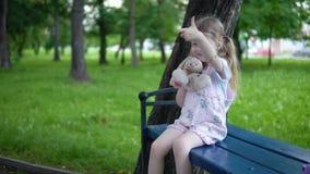 Μικρό κορίτσι με μια συνεδρίαση λαγουδάκι παιχνιδιών σε έναν πάγκο πάρκων σε μια νεφελώδη ημέρα φιλμ μικρού μήκους