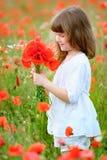 Μικρό κορίτσι με τα άγρια κόκκινα λουλούδια στον τομέα Στοκ Εικόνα