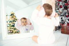 Μικρό κορίτσι με τα ακουστικά που κοιτάζει στον καθρέφτη απομονωμένη Χριστούγεννα διάθεση τρία σφαιρών λευκό Στοκ Εικόνα
