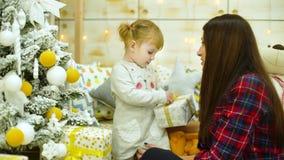 Μικρό κορίτσι με τα ανοίγοντας κιβώτια δώρων μητέρων κοντά στο χριστουγεννιάτικο δέντρο στο σπίτι φιλμ μικρού μήκους