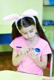 Μικρό κορίτσι με τα αυγά Πάσχας αυτιών λαγών χρωμάτων Στοκ Εικόνες