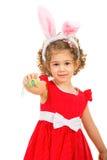 Μικρό κορίτσι με τα αυτιά λαγουδάκι που δίνουν το αυγό Πάσχας Στοκ Φωτογραφίες