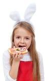 Μικρό κορίτσι με τα αυτιά λαγουδάκι που τρώει ένα σάντουιτς Στοκ Εικόνες