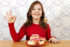 Μικρό κορίτσι με τα γλυκά donuts και το εντάξει σημάδι χεριών Στοκ Εικόνα