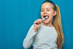 Μικρό κορίτσι με τα μακριά ξανθά καθαρίζοντας δόντια τρίχας με το οδοντωτό bru Στοκ Φωτογραφίες