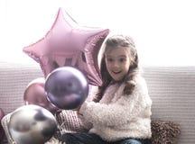 Μικρό κορίτσι με τα μπαλόνια που κάθεται στον καναπέ στοκ εικόνες