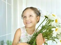Μικρό κορίτσι με τα λουλούδια dasies Στοκ Φωτογραφία