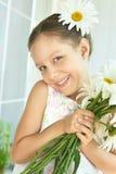 Μικρό κορίτσι με τα λουλούδια dasies Στοκ Εικόνα
