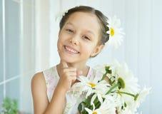 Μικρό κορίτσι με τα λουλούδια dasies Στοκ Φωτογραφίες