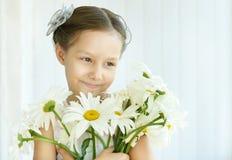 Μικρό κορίτσι με τα λουλούδια dasies Στοκ φωτογραφία με δικαίωμα ελεύθερης χρήσης