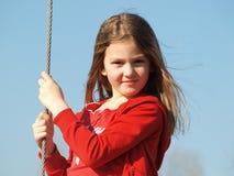 Μικρό κορίτσι με τα ρέοντας ξανθά μαλλιά σε ένα κόκκινο πουλόβερ ενάντια στο μπλε ουρανό στοκ εικόνα